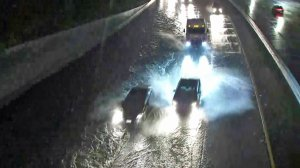 Drivers try to avoid a flooded portion of the 5 Freeway near the 110 Freeway on Dec. 23, 2019. (Credit: KTLA)