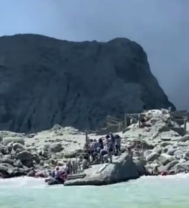 People are seen seeking refuge on the beach during a volcanic eruption on New Zealand's White Island on Dec. 9, 2019. (Credit: @sch on Twitter)