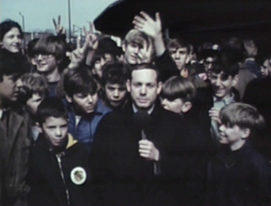 A young, excited Cubs fans throws up peace signs and waves at the camera behind a WGN reporter on Opening Day, April 8, 1969.​