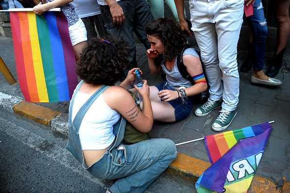 """A injured woman lies on ground after Turkish riot police used tear gas during the Gay Pride parade on June 28, 2015 in the Istiklal street near the Taksim square in Istanbul. Riot police in Istanbul used teargas and water cannon to disperse thousands of participants in the Gay Pride parade in the Turkish city, an AFP reporter said. Police took action against the crowd when demonstrators began shouting slogans accusing the social conservative President Recep Tayyip Erdogan of """"fascism"""". AFP PHOTO / OZAN KOSE        (Photo credit should read OZAN KOSE/AFP/Getty Images)"""