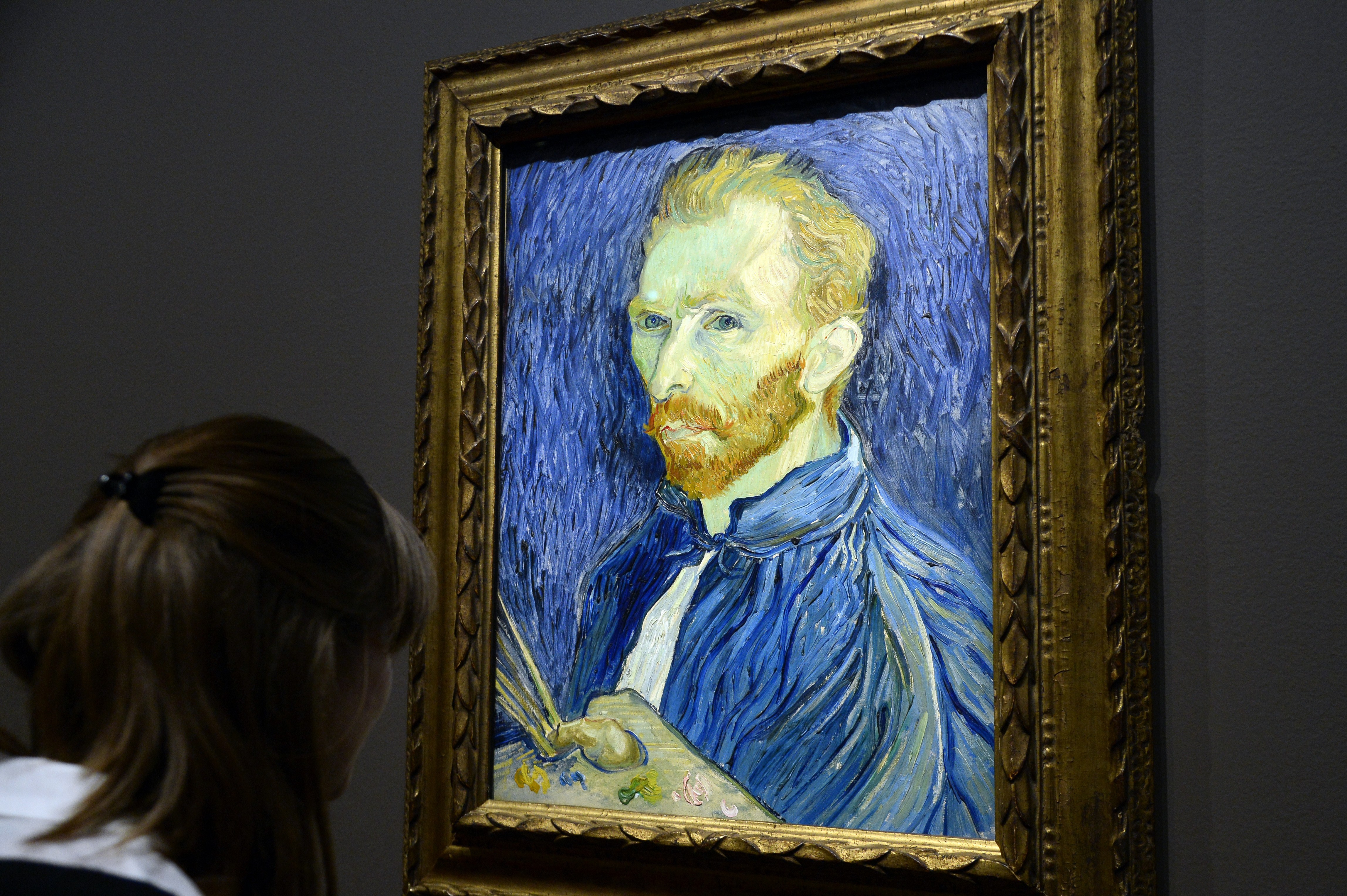 """A visitor looks at a self-portrait by late Dutch painter Vincent Van Gogh displayed at the Orsay Museum as part of the exhibition """"Van Gogh/Artaud. The Man Suicided by Society"""", on March 10, 2014 in Paris. AFP PHOTO / BERTRAND GUAY (Photo credit should read BERTRAND GUAY/AFP/Getty Images)"""
