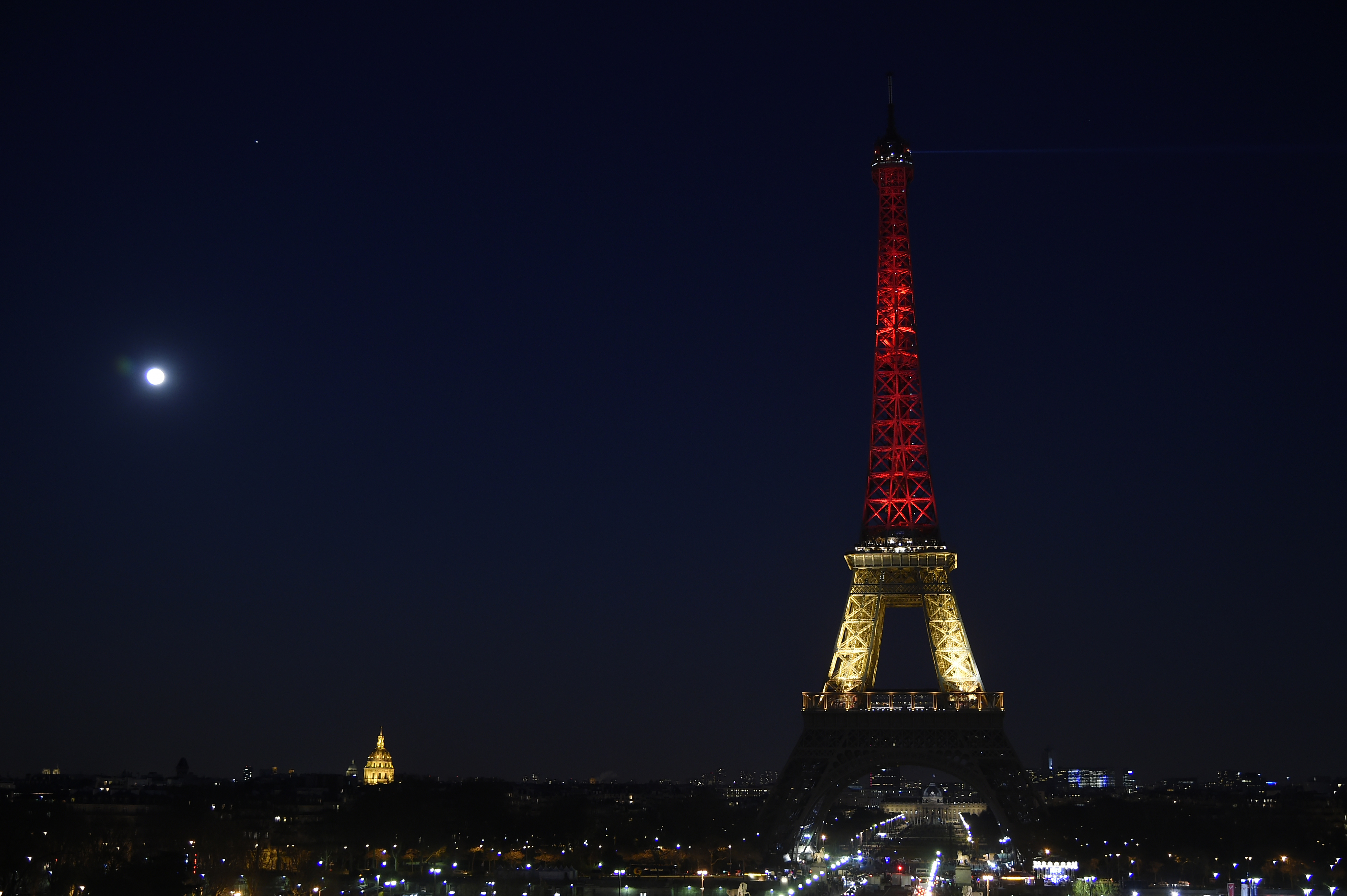 A picture taken on March 22, 2016 shows the Eiffel Tower in Paris illuminated in colours of the Belgian flag in tribute to the victims of terrorist attacks in Brussels. Photo credit should read LIONEL BONAVENTURE/AFP/Getty Images