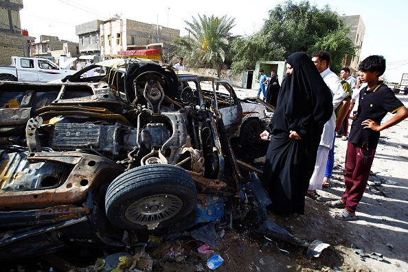 Iraqis look at the damage following a twin suicide bombing attack, claimed by the Islamic State (IS) group, in the southern Iraqi city of Samawah, situated deep in Iraq's Shiite heartland, on May 1, 2016. (HAIDAR HAMDANI/AFP/Getty Images)
