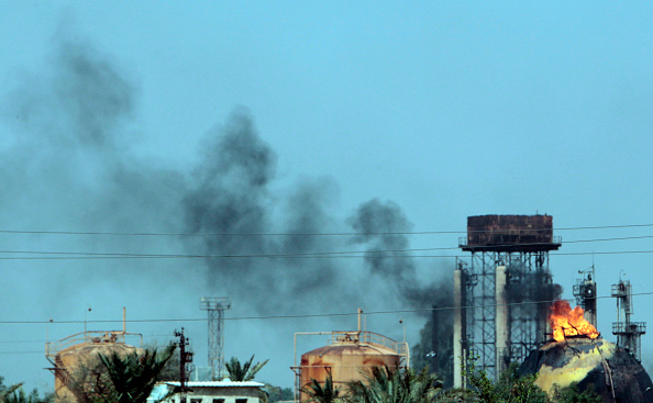 A picture taken on May 15, 2016 shows flames and smoke rising from tanks after a suicide bomb attack on the Taji gas plant, about 20 kilometres (12 miles) north of the Iraqi capital Baghdad.(SABAH ARAR/AFP/Getty Images)