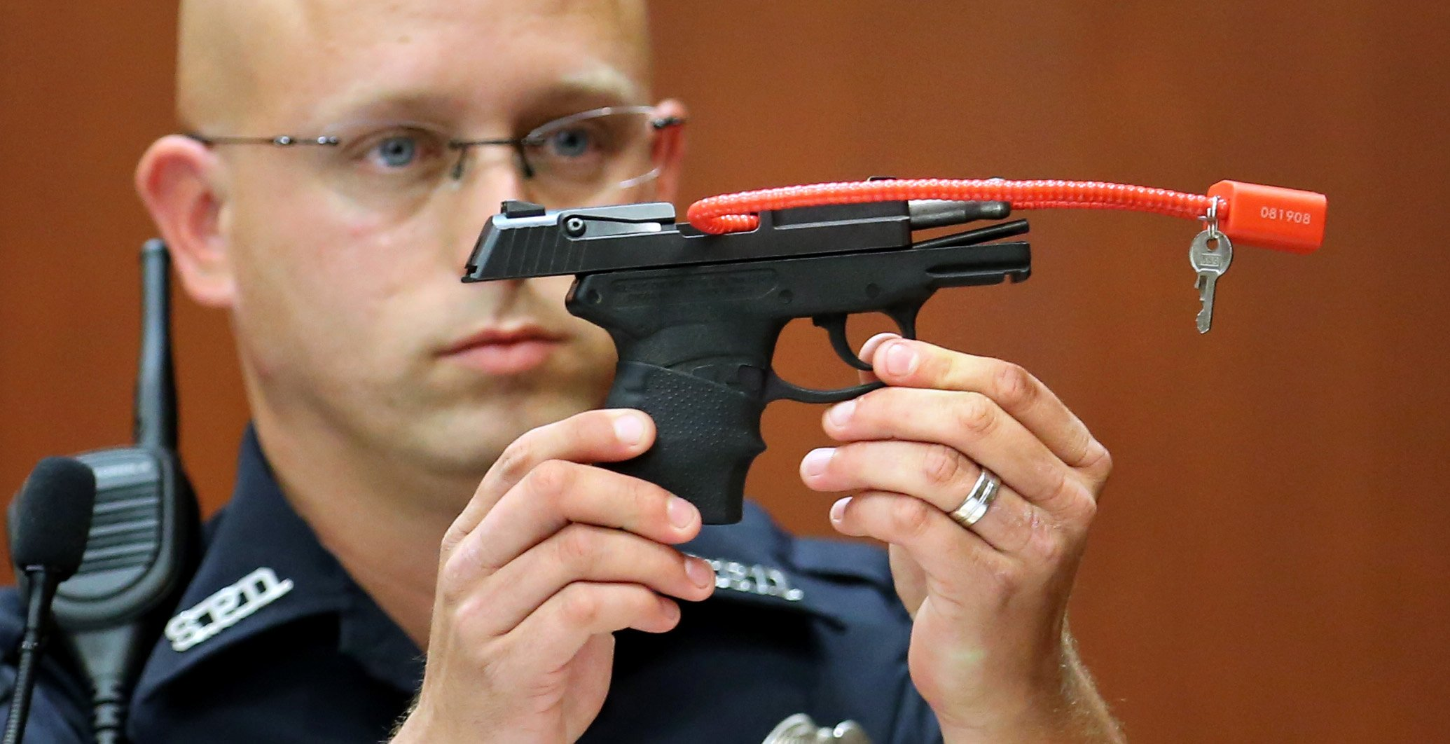 Sanford police officer Timothy Smith holds up the gun that was used to kill Trayvon Martin, while testifying in the 15th day of the George Zimmerman trial, in Seminole circuit court in Sanford, Fla., Friday, June 28, 2013. Zimmerman is accused in the fatal shooting of Trayvon Martin. Photo credit:  Joe Burbank/POOL