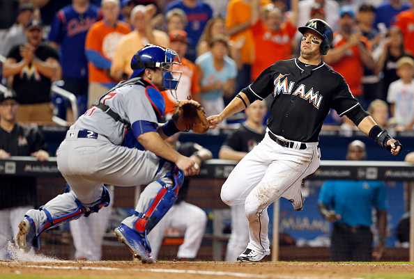 The Miami Marlins' Martin Prado scores behind Chicago Cubs catcher Miguel Montero in the fifth inning on a single by Giancarlo Stanton at Marlins Park in Miami on Saturday, June 25, 2016. The Marlins won, 9-6. (Al Diaz/Miami Herald/TNS via Getty Images)