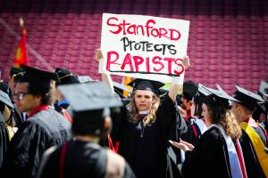 A woman carries a sign in solidarity for a Stanford rape victim during graduation at Stanford University, in Palo Alto, California, on June 12, 2016. Stanford students are protesting the universitys handling of rape cases alledging that the campus keeps secret the names of students found to be responsible for sexual assault and misconduct. (Photo credit should read GABRIELLE LURIE/AFP/Getty Images)