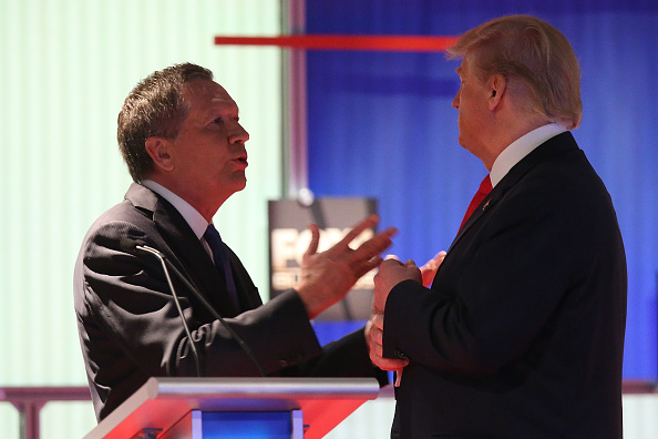 Republican presidential candidates (L-R) Ohio Governor John Kasich and Donald Trump talk during a commercial break during the Fox Business Network Republican presidential debate at the North Charleston Coliseum and Performing Arts Center on January 14, 2016 in North Charleston, South Carolina. (Photo by Scott Olson/Getty Images)
