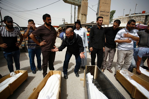 Iraqi men mourn over bodies after they lost five members of their family in a suicide bombing that ripped through Baghdad's busy shopping district of Karrada, during their funeral in the holy Iraqi city of Najaf on July 3, 2016. The blast hit the Karrada district early in the day as the area was packed with shoppers ahead of this week's holiday marking the end of the Muslim fasting month of Ramadan, killing at least 75 people in the deadliest single attack this year in Iraq's capital. / AFP / Haidar HAMDANI (Photo credit should read HAIDAR HAMDANI/AFP/Getty Images)