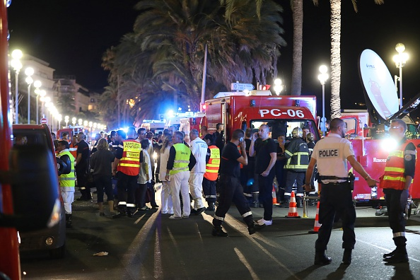 """Police officers, firefighters and rescue workers are seen at the site of an attack on July 15, 2016, after a truck drove into a crowd watching a fireworks display in the French Riviera town of Nice. A truck ploughed into a crowd in the French resort of Nice on July 14, leaving at least 60 dead and scores injured in an """"attack"""" after a Bastille Day fireworks display, prosecutors said on July 15. (Photo credit: VALERY HACHE/AFP/Getty Images)"""