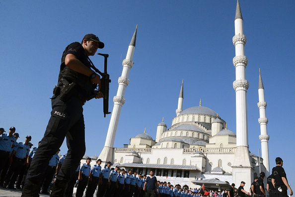 An armed Turkish police officer stands guard during a funeral ceremony for victims of the failed July 15 coup attempt at Kocatepe Mosque in Ankara on July 17, 2016. (ILYAS AKENGIN/AFP/Getty Images)