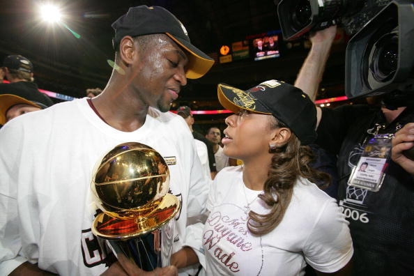 Finals MVP Dwyane Wade #3 of the Miami Heat celebrates with his wife Siohvaughn Wade and the MVP trophy as he walks off the court after the Heat beat the Dallas Mavericks 95-92 in Game Six of the 2006 NBA Finals June 20, 2006 at American Airlines Center in Dallas, Texas. (Photo by Victor Baldizon/NBAE/Getty Images)