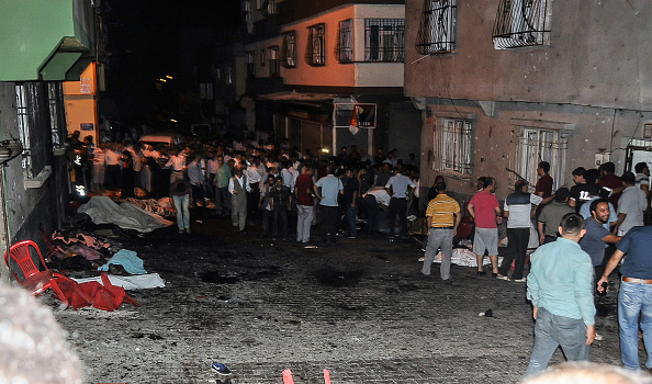 Bodies are covered as people gather at the explosion site on August 20, 2016 in Gaziantep, in a late night militant attack on a wedding party in southeastern Turkey.  The governor of Gaziantep said 22 people are dead and 94 injured in the late night militant attack.  (STR/AFP/Getty Images)
