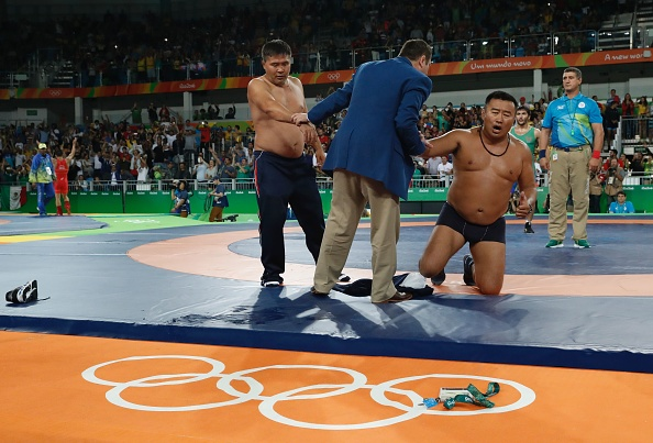 Mongolia's Mandakhnaran Ganzorig's coaches react after the judges announced that Uzbekistan's Ikhtiyor Navruzov won folling a video replay in their men's 65kg freestyle bronze medal match on August 21, 2016, during the wrestling event of the Rio 2016 Olympic Games at the Carioca Arena 2 in Rio de Janeiro. (JACK GUEZ/AFP/Getty Images)