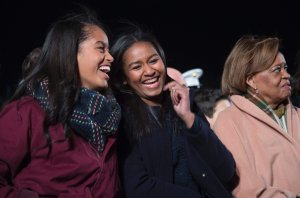 First daughters Malia (L) and Sasha (C) share a laugh on the Ellipse of the National Mall December 3, 2015 in Washington, DC. The First Family was joined by celebrities and guests to light the National Christmas tree during an evening of performances. AFP PHOTO / JIM WATSON / AFP / JIM WATSON (Photo credit should read JIM WATSON/AFP/Getty Images)