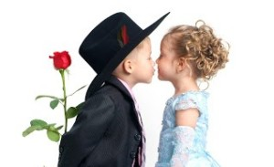 Little pretty boy with rose kisses girl in blue dress