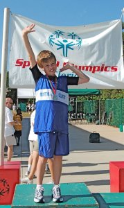 Inspiring an athlete -- Here, a 12-year-old John shows off his first-place medal for the 100 meters at the Special Olympics Summer State Games in 2008.