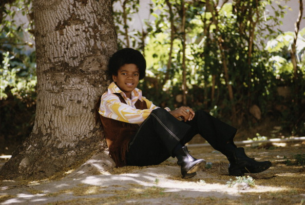 American singer Michael Jackson (1958 - 2009) relaxes under a tree, April 1970. (Photo by Michael Ochs Archives/Getty Images)