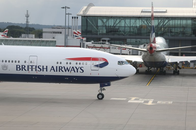 A British Airways 777 taxis near a terminal building.