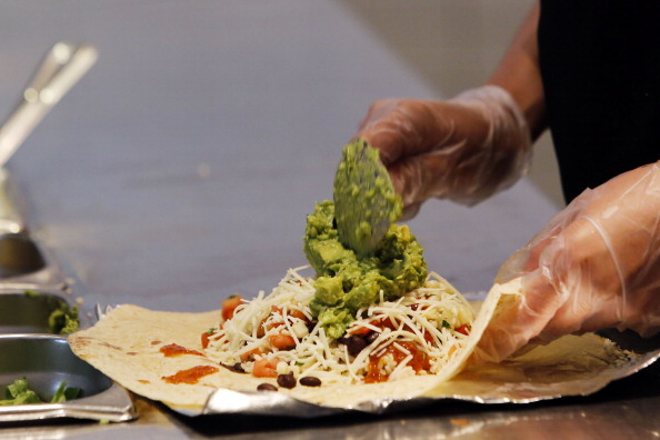 An employee prepares a Chipotle Mexican Grill burrito at the Sunset and Vine store in Hollywood, California, U.S., on Tuesday, July 16, 2013. Chipotle Mexican Grill Inc. is scheduled to release earnings data on July 18. Photographer: Patrick T. Fallon/Bloomberg via Getty Images