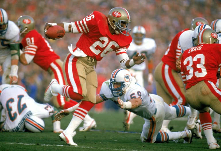 STANFORD, CA - JANUARY 20: Wendell Tyler #26 of the San Francisco 49ers works to escape a tackle during Super Bowl XIX against the Miami Dolphins at Stanford Stadium on January 20, 1985 in Stanford, California. The 49ers defeated the Dolphins 38 to16. (Photo by Tony Duffy/Getty Images)