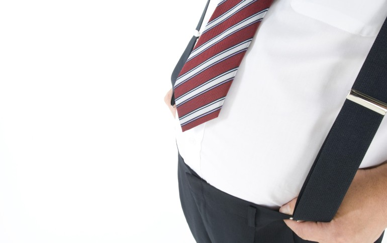 Overweight businessman with a pot belly holding his suspenders