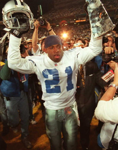 TEMPE, AZ - JANUARY 28: Dallas Cowboys cornerback Deion Sanders hoists the Vince Lombardi Super Bowl trophy as he walks off the field to the locker room after defeating the Pittsburgh Steelers 28 January during Super Bowl XXX at Sun Devil Stadium in Tempe, Arizona. The Cowboys won 27-17. (Photo credit should read VINCE BUCCI/AFP/Getty Images)