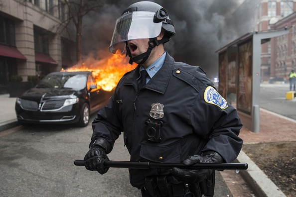 WASHINGTON, USA - JANUARY 20: Anti-Trump protestors set a limousine on fire during clashes with police after President Trump was sworn into office in Washington, USA on January 20, 2017. (Photo by Samuel Corum/Anadolu Agency/Getty Images)