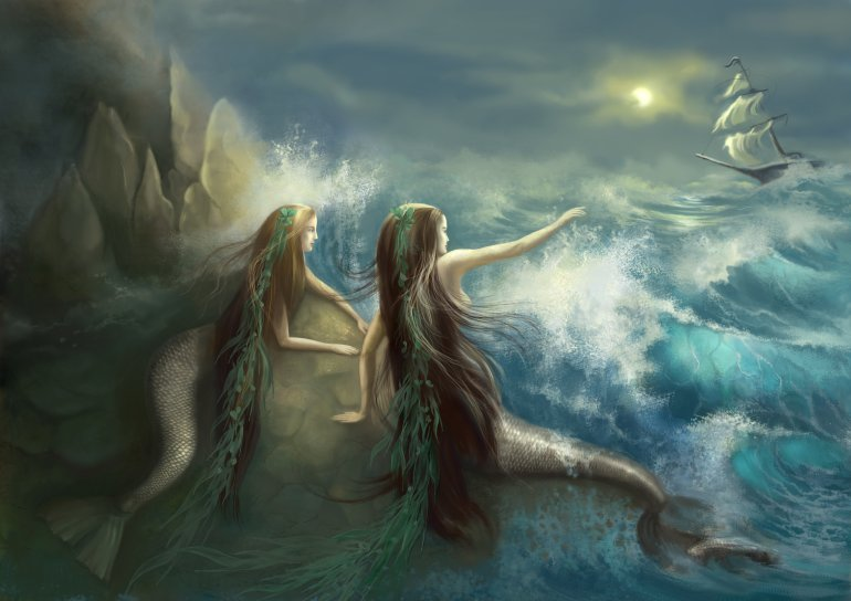 Hunting two mermaids in the rocks on the background of a stormy ocean and the raging waves. Getty