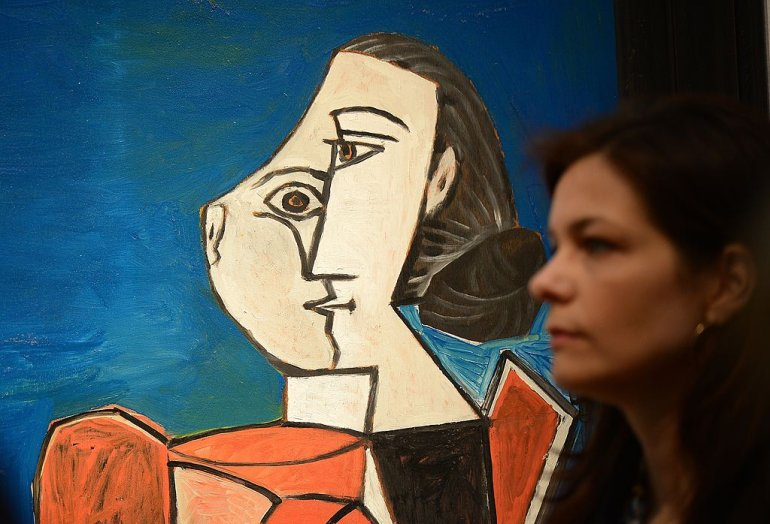"""Femme assise en costume rouge sur fond bleu"" by Pablo Picasso is on display during a preview of Christie's Impressionist and Modern Art sales in New York on May 3, 2013. Christie's is scheduled to hold its Impressionist and Modern Art sales May 8-9. AFP PHOTO/Emmanuel Dunand ++RESTRICTED TO EDITORIAL USE, MANDATORY MENTION OF THE ARTIST UPON PUBLICATION, TO ILLUSTRATE THE EVENT AS SPECIFIED IN THE CAPTION++ (Photo credit should read EMMANUEL DUNAND/AFP/Getty Images)"